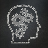 Education concept: Head With Gears on chalkboard background
