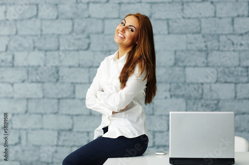 happy businesswoman sitting at the table with arms folded