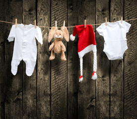 .Baby clothes and santa hat on a clothesline, wooden background