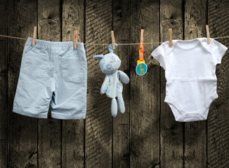 Baby boy clothes and stuffed bunny on a clothesline