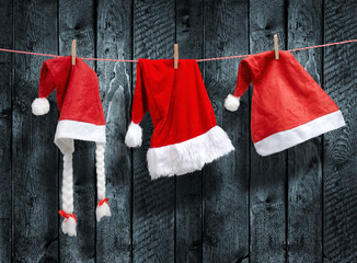 Three Santa Claus hat hanging on a clothesline