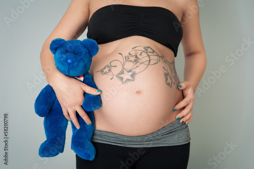 Pregnant woman holding teddy bear.