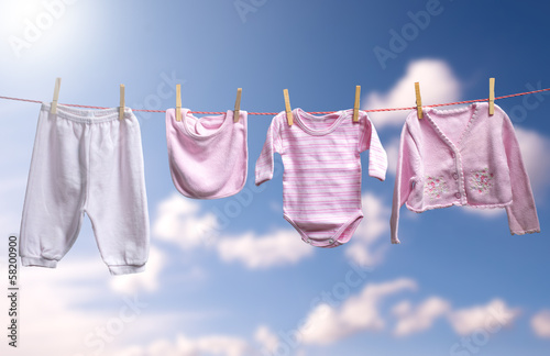 Clean baby girl clothes on the outdoor clothesline.
