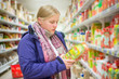 Young woman select juices on shelves in supermarket