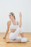 Serious ponytailed woman sitting on floor stretching her body poster