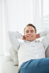 Smiling relaxed young man lying on sofa