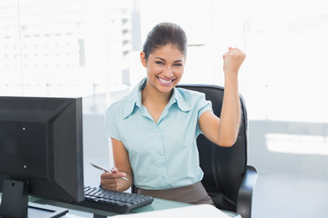 Happy businesswoman clenching fist at office desk