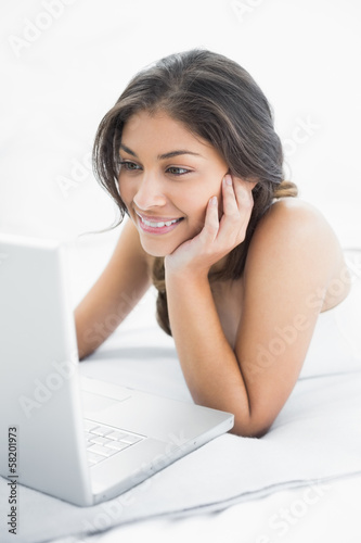 Smiling casual woman using laptop in bed