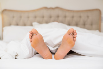 Bare feet in bed at home