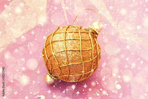 golden christmas ball on a pale pink background