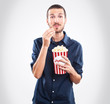 Young man watching a movie and eating popcorn