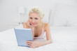 Smiling casual young blond with tablet PC in bed