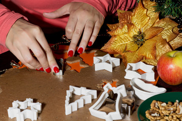 Woman's hands cutting gingerbread christmas cookies.