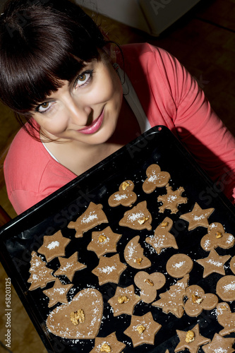 Beautiful young woman holding baking tray with gingerbread cooki