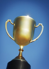 Gold trophy cup against blue