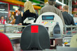 Empty cash desk and queue of customers on back in supermarket