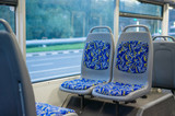 Blue seat places in modern city trolley bus on back side