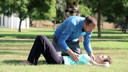 Young woman doing crunches in park with help of personal trainer