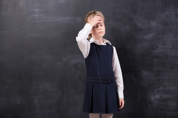 schoolgirl with headache stands at the blackboard