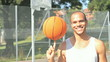 Basketball player spinning a basketball outdoors