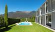 Leinwanddruck Bild - Modern villa with pool, view from the garden