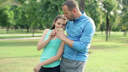 Young sporty couple eating apple talking in the park