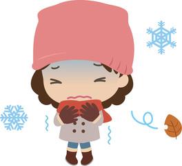 寒さで震えるコート姿の女性