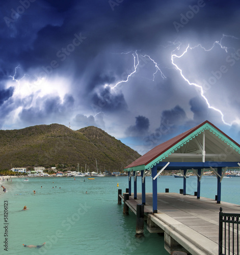 Thunderstorm over beautiful beach with jetty over water
