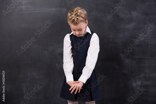 Sad little schoolgirl near blackboard