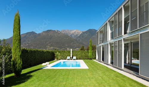 Leinwanddruck Bild Modern villa with pool, view from the garden