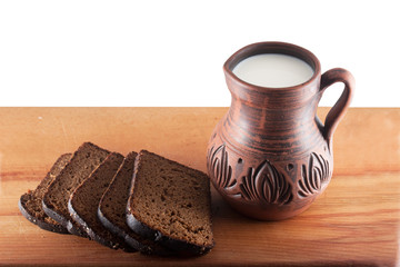 broad and pitcher of milk on a wooden table