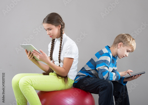 Children sitting on a big rubber ball with Pad Tablet PC