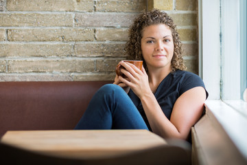 Woman With Coffee Mug Sitting In Cafeteria