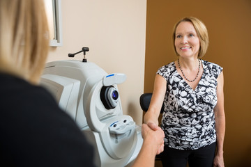 Optician And Patient Shaking Hands In Clinic