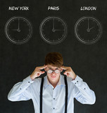 Businessman with chalk time zone clocks on blackboard background