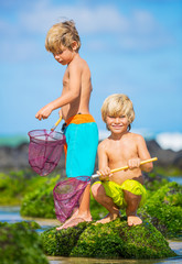 Happy young kids playing at the beach on summer vacation
