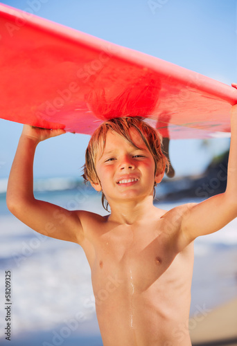 happy young boy at the beach with surfboard