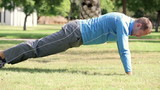 Young man doing push-ups on a grass in the park