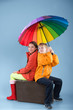Children with a colorful umbrella sitting on old traveling bag