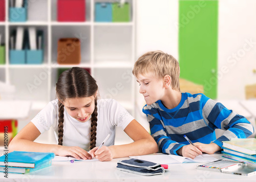 Schoolgirl writing a test and boy looking at her copybook