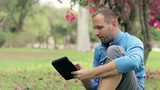 Young sportsman using tablet sitting on grass in the park