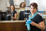 Customer Holding Coffee Cup With Workers At Café
