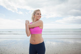 Smiling toned woman exercising on beach