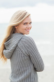 Cute young woman in gray knitted jacket on beach