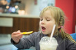 Adorable girl have meal in fast food restaurant