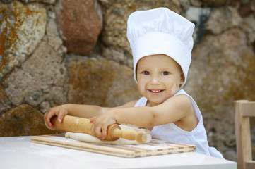 cute little boy with chef hat cooking