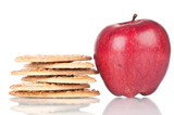 Biscuits and red apple over a white reflective background