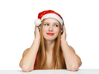Young woman in santa claus hat and headphones isolated on white