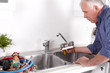 Plumber in kitchen with a wrench.