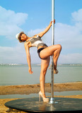Young woman exercise pole dance.